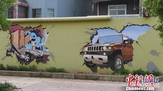 """图为""""吓人""""的3D车祸壁画。  近日,广西南宁市五象大道路边的墙上出现了一幅""""恐怖""""壁画——一辆越野车破墙而出的3D立体壁画,因过于逼真而让一些路人感到不适。这幅3D 车祸壁画被当地媒体报道后,城管部门以""""违反户外广告条例""""为由,责令壁画的主人48小时内将墙壁恢复原样。 4月9日下午,记者来到现场看到一堵墙被染成浅黄色,墙上画着一辆越野车的半个车身冲破墙壁,车子卡在墙里,墙壁裂缝四起,画面非常逼真。而越野车的"""